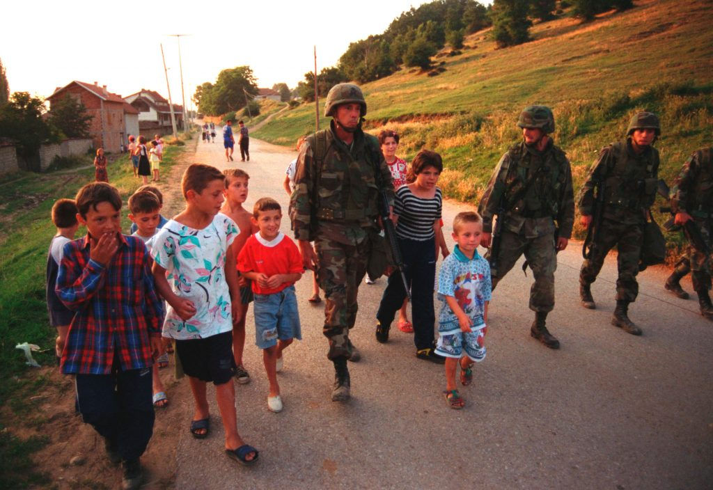 990628-M-5696S-025_-_U.S._Marines_march_with_local_children_down_street_of_Zegra_Kosovo-1024x704.jpg